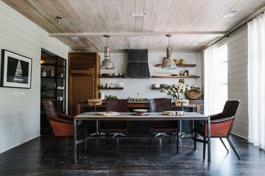 modern farmhouse cabinetry in room with reclaimed wood industrial kitchen island and rustic dining table