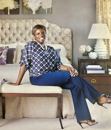photograph of designer iantha carley sitting on chair near bed