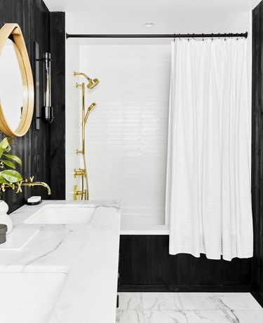 art deco bathroom by Emily Henderson Design with black walls and marble floor