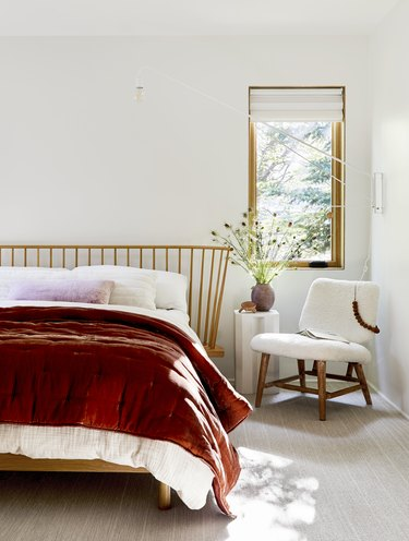 natural decor in white room with wooden bed and red quilt