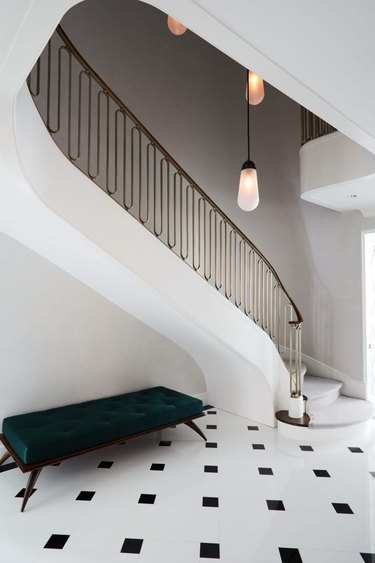 art deco staircase with modern light fixture and brass railing