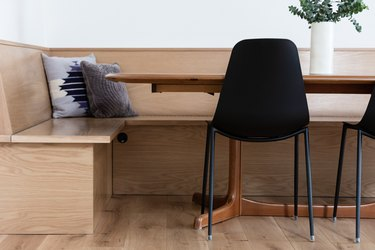 wooden banquette surrounding table with black chairs