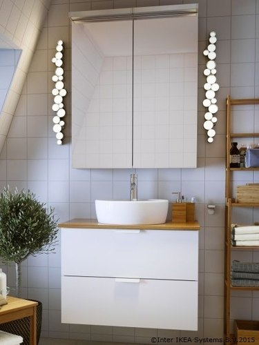 IKEA bathroom lighting idea with bubble-style wall lights and white wall tile