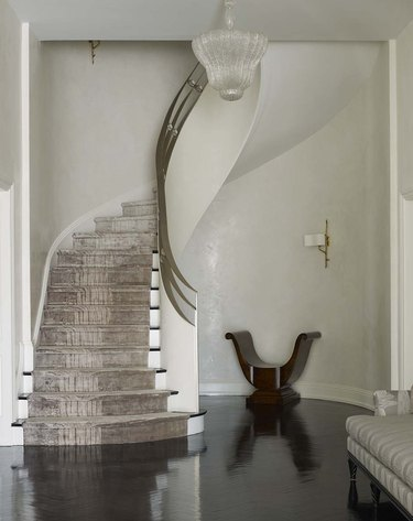 art deco staircase with brass railings and velvet carpet