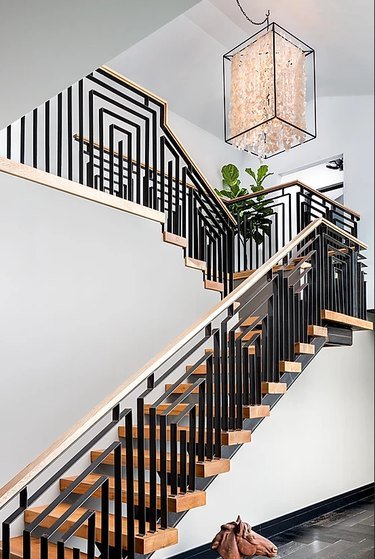 Art Deco staircase with black geometric railings and large pendant light