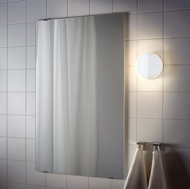 IKEA bathroom lighting idea with white tile wall and wall light