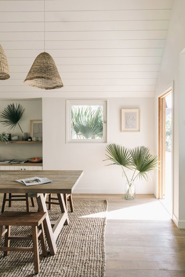 natural decor in white dining room with palms in a vase