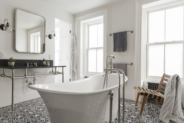 art deco bathroom by Elizabeth Roberts Architecture with freestanding tub and console sink
