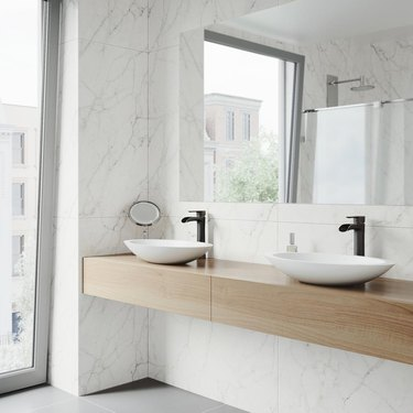 bathroom space with marble walls and two sinks