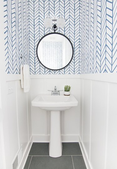 bathroom space with blue and white wallpaper and round mirror