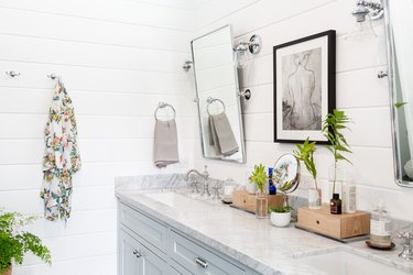 modern bathroom with tilted mirrors over double vanity