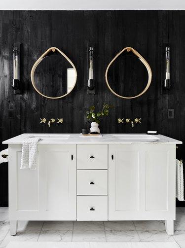 modern bathroom with teardrop mirrors over double vanity