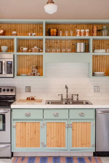 kitchen sink with double handle faucet and mint blue and wood-colored cabinets