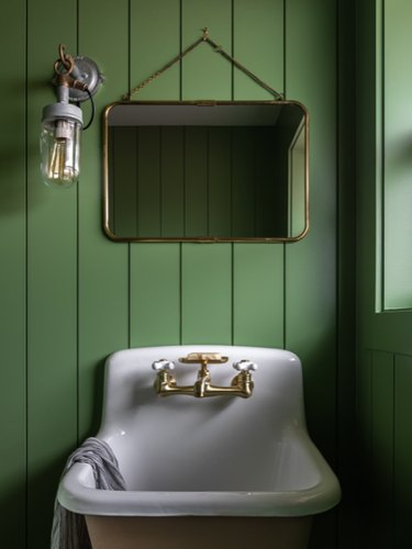 rustic bathroom lighting idea with wall sconce near mirror on green shiplap wall