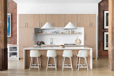kitchen with light wood, white chairs and white lighting fixtures
