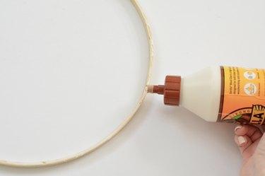 Wood glue being applied to wooden hoop.