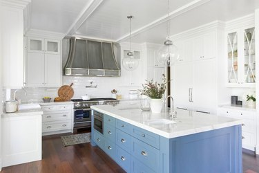 blue kitchen island in all-white space with dark wood flooring
