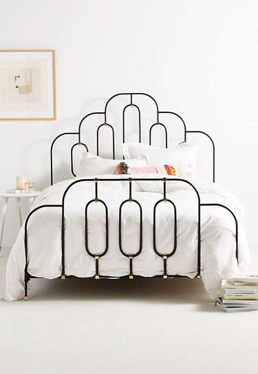 art deco bedroom with iron bed frame with gold detail