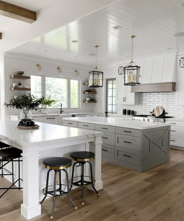 large white kitchen with gray island and marble island