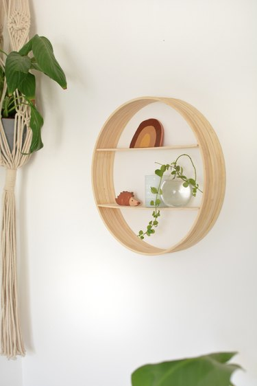 Wooden circle with small trinkets on shelves hanging on wall.