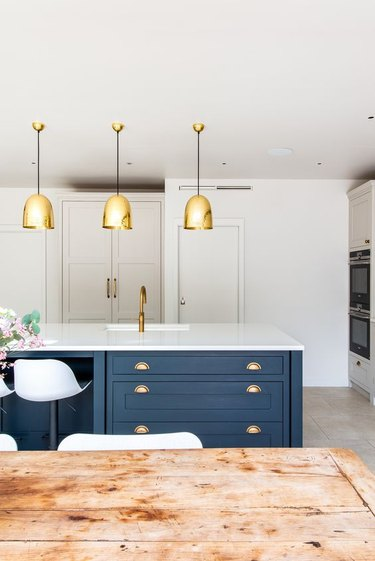 blue kitchen island with brass accents and white countertop