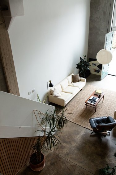 loft apartment with cement floors and hanging Noguchi lamp