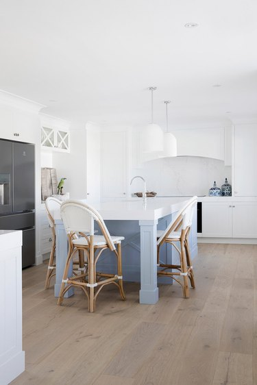 pale blue kitchen island with all white cabinets and countertops