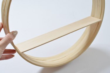 Wooden shelf placed inside circular frame