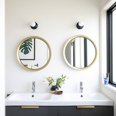 Navy blue coastal bathroom lighting idea above circular mirrors in white bathroom