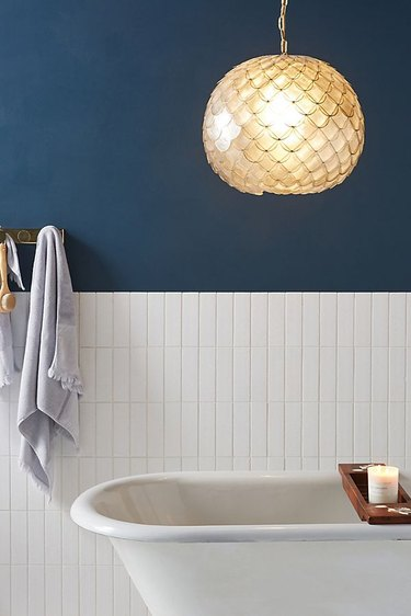 Capiz coastal bathroom lighting idea in white and navy blue bathroom