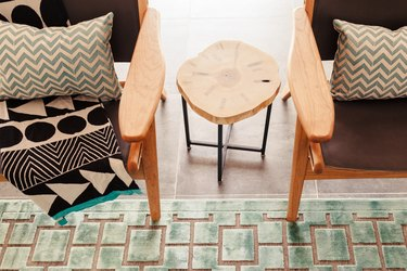 pair of living room chairs accented by geometric rug and patterned pillows in a midcentury modern family room