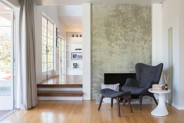 calm, luxurious entryway with minimal cement fireplace facade