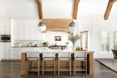 Dark wood farmhouse kitchen floor with white cabinets and exposed ceiling beams