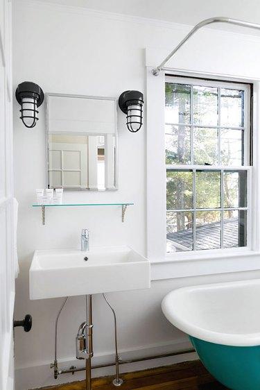 Industrial metal guard coastal bathroom lighting idea in white and turquoise bathroom
