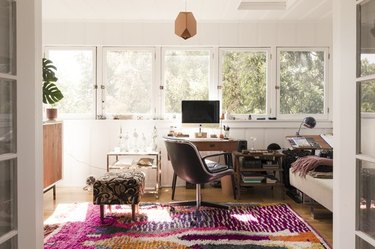 global patterns and bold colors in a tree-lined apartment living room