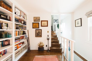 quaint cottage with bookcase library and dark wooden floors in stairway