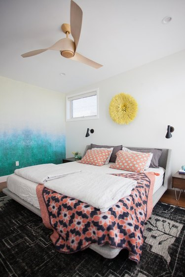 pattern-filled bedroom with modern ceiling fan and wall sconces