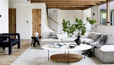 midcentury modern family room design by Emily Henderson with a natural wood side table and grey l-shaped couch.