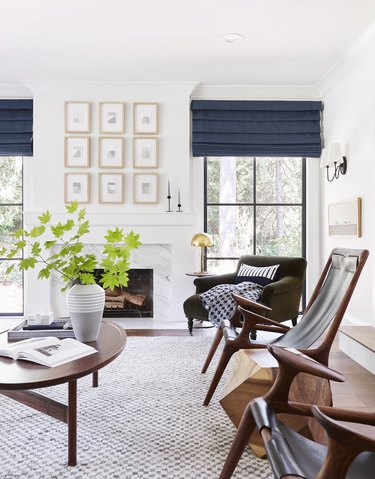 Bright midcentury modern family room design by Emily Henderson with oval wooden table and matching leather sitting chairs.