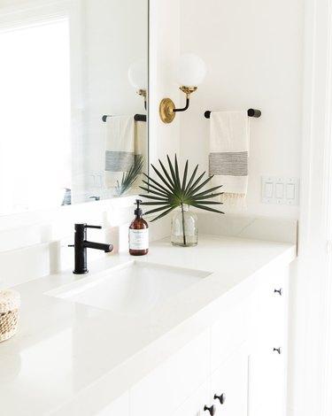 Brass globe-style coastal bathroom lighting idea in all-white bathroom with palm frond