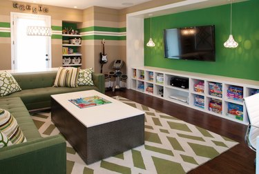 family room ideas with TV mounted on green wall with built in cubbies