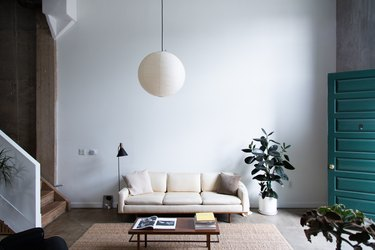 midcentury modern family room with white couch, suspended globe lamp, and teal door.