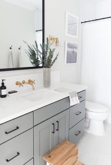 Traditional brass coastal bathroom lighting idea in white and gray bathroom
