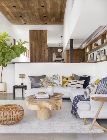 coastal living room with wood ceiling, concrete floors, tree trunk coffee table, white sectional with multi colored throw cushions, cane pouf, fiddle leaf fig plant.