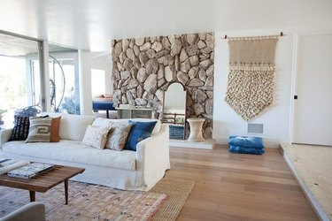 midcentury interior with neutral color palette and rock fireplace