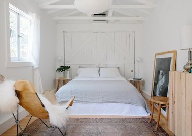 breezy bedroom with white linens and hanging paper lamp