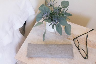 Gray linen eye pillow on top of nightstand with eyeglasses and flowers