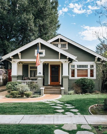 Green Craftsman home exterior with white trim and columns