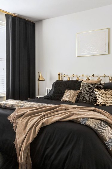 art deco bedroom with shimmering throw pillows on bed and brass fixtures