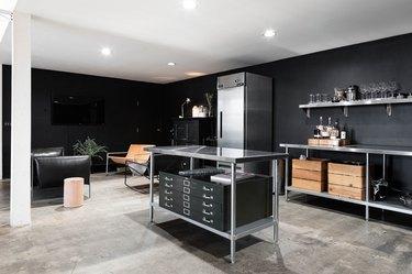 stainless steel kitchen island with black storage bins in black kitchen